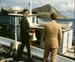 Jack Lord and James MacArthur on the pier beside a small boat