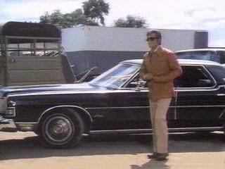 JL arrives on  location. The 1974 Marquis. The blue and white truck in the background is one of the prop trucks. the leather jacket appeared only in Requiem for a Saddle Bronc Rider.Therefore, this was taken in Waimanelo